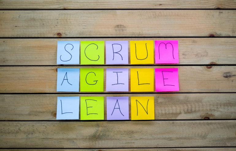A wooden board with sticky notes spelling out the words scrum agile & lean. The post-it notes spell out the management technique used with scurm agile and lean start-up.